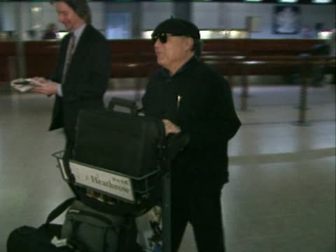 actor danny devito pushes a trolley laden with luggage as he flies out through heathrow airport talks to a reporter as he travels dressed all in black - luggage trolley stock videos & royalty-free footage