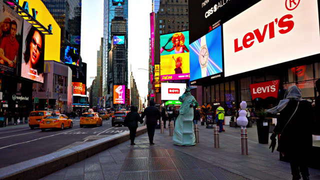 actor dressed as statue of liberty in times square. people walk by in theater district. - 俳優点の映像素材/bロール