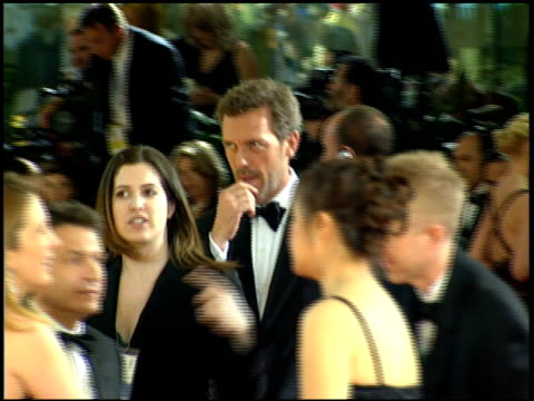 Actor Hugh Laurie walking through red carpet on Beverly Hilton hotel waving