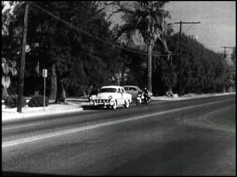actor jimmy stewart narrates this wide shot of a teenager in a 1954 chevrolet getting pulled over by a motorcycle cop 1950s teenager pulled over by... - narrating stock videos & royalty-free footage