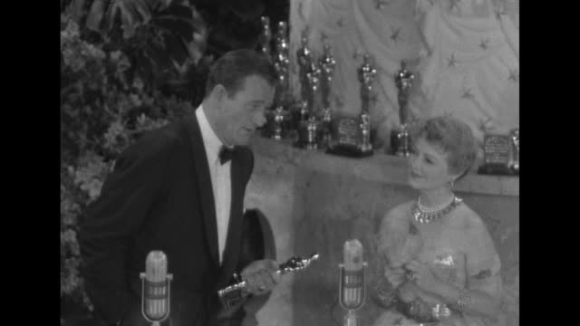 actor john wayne accepts best actor oscar for actor gary cooper, who is not present, as presenter janet gaynor looks on; sot wayne, as he holds... - academy awards video stock e b–roll
