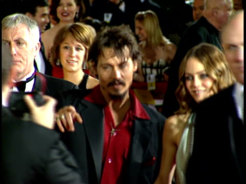 Actor Johnny Depp girlfriend French singer Vanessa Paradis walking through red carpet at Beverly Hilton hotel posing for photographs waving to press