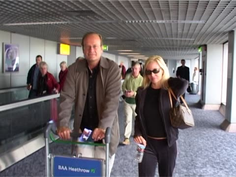 actor kelsey grammer arrives at heathrow from los angeles with wife camille grammer / the star of cheers and frasier pushes trolley holding inflight... - luggage trolley stock videos & royalty-free footage