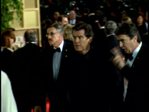 actor pierce brosnan walking quickly through red carpet at beverly hilton hotel w/ group of people - pierce brosnan stock videos and b-roll footage