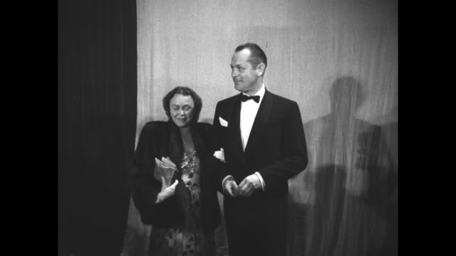 actor robert montgomery poses for photos with his wife, elizabeth allen montgomery, inside the shrine auditorium at the 19th academy awards; pan bank... - shrine auditorium stock videos & royalty-free footage