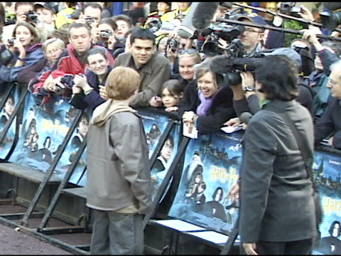 stockvideo's en b-roll-footage met day * handheld actor rupert grint agent females walking on walkway at leicester square grint talking to press behind barricades - 2001