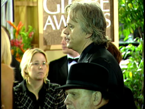 Actor Tim Robbins walking along crowded red carpet at Beverly Hilton hotel