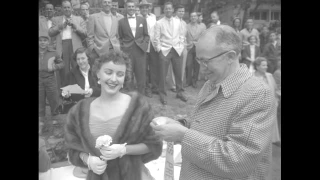 ms actor walter brennan wearing a tweed overcoat kisses miss albany jane towery who removes her mink stole displaying a miss albany sash and brennan... - chest kissing stock videos & royalty-free footage
