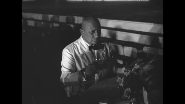 actor/director erich von stroheim, seated at table and dressed in evening wear, takes a glass from opposite side of table and raises it in a toast to... - カンヌ映画祭点の映像素材/bロール