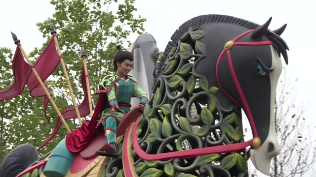 Actors dressed in costume as the characters Anya and Elsa from Frozen perform on top of a float during a parade at Walt Disney Co's Shanghai...