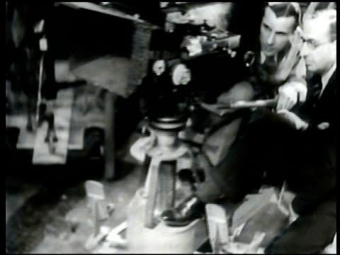 vídeos de stock, filmes e b-roll de hollywood actors frances lederer and ginger rogers talking w/ director camera cranes forward ext projection room door int screening room w/ iris... - 1930 1939