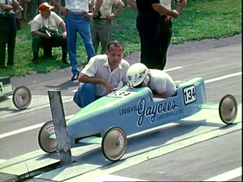 vídeos y material grabado en eventos de stock de actors lloyd haynes and james drury and apollo astronaut dick gordon jr sitting in soap box cars at starting line during prerace festivities of... - c119gs