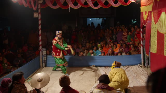 vídeos de stock, filmes e b-roll de actors perform in a traditional play about a tiger and bonbibi, guardian spirit of the forests, as a captivated audience watches, the sundarbans, india. - roupa quente