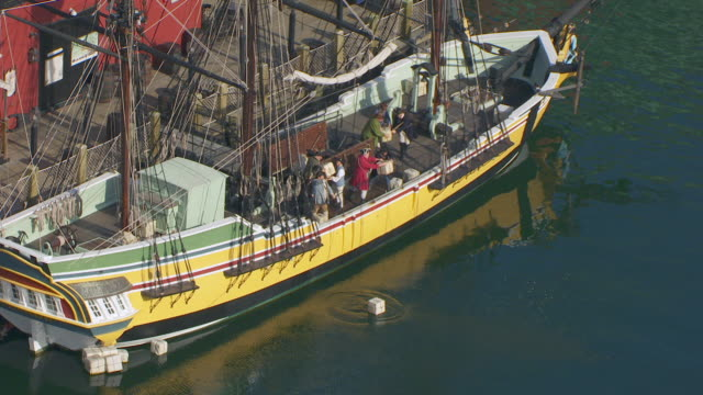 WS ZI AERIAL POV Actors with period costume in replica ship throwing tea packages / Boston, Massachusetts, United States