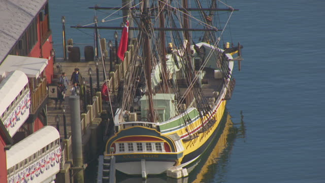 MS AERIAL POV Actors with period costume in replica ship throwing tea packages / Boston, Massachusetts, United States