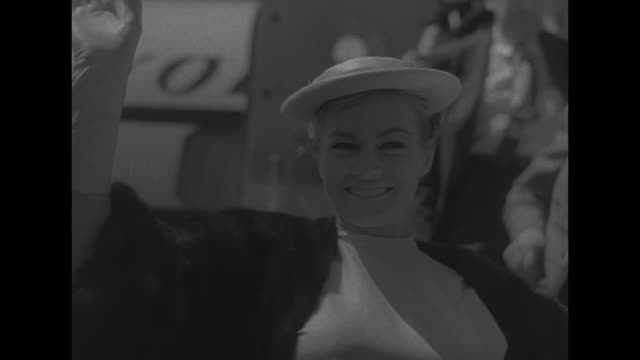 actress anita ekberg pauses on airstairs as she deplanes at rome's ciampino airport she removes her sunglasses / cu ekberg smiles waves speaks from... - ciampino airport video stock e b–roll