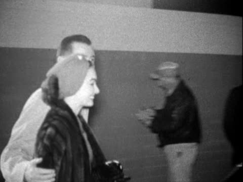 stockvideo's en b-roll-footage met actress ann blyth walking with husband dr james mcnulty at airport, walking along tarmac at night; ms blyth wears fur coat / ann blyth and dr... - winterjas