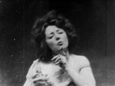 B/W 1902 actress Anna Held holding glass of champagne + talking in drunken manner / newsreel