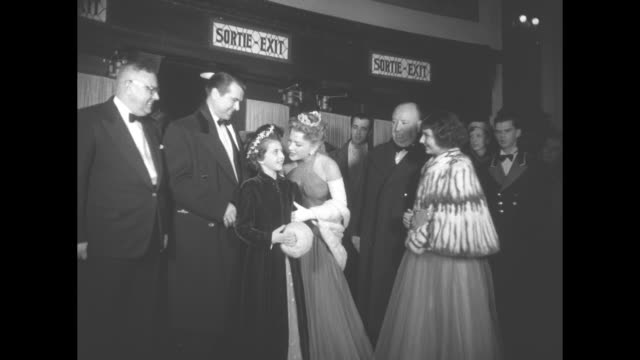 vidéos et rushes de ws actress anne baxter and actor roger dann appear at film premiere and stand inside theater with young quebecois girls carmen gringos and renne... - première de film