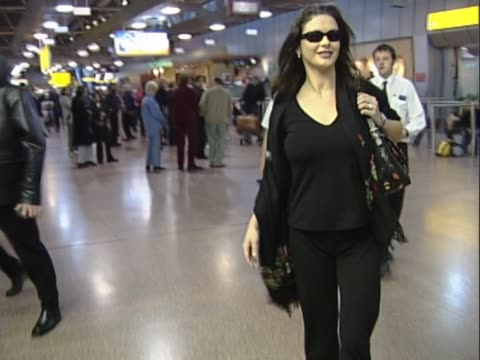 actress catherine zeta jones arrives at heathrow showing signs of pregnancy. walks confidently for cameras and out to car. fiance michael douglas... - catherine zeta jones video stock e b–roll