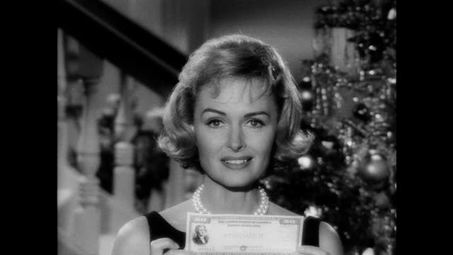 / Actress Donna Reed in cocktail dress standing in front of Christmas tree / table with working train set / Reed stops train and speaks directly to...