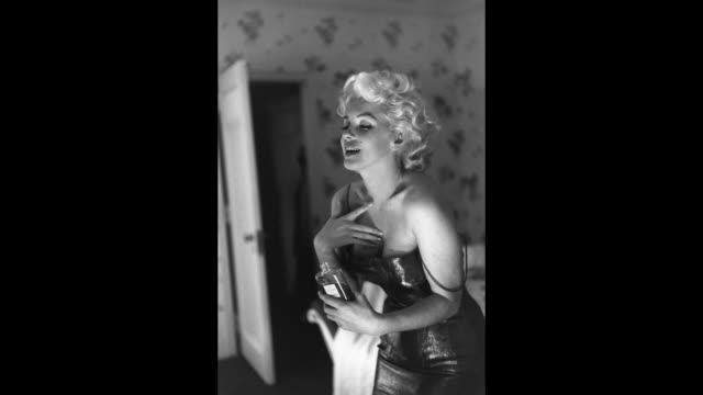 stockvideo's en b-roll-footage met gif actress marilyn monroe gets ready to go see the play 'cat on a hot tin roof' playfully applying her make up and chanel no 5 perfume on march 24... - marilyn monroe