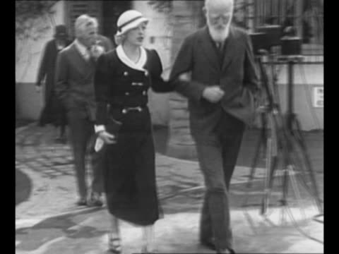 actress marion davies approaches, walks arm-in-arm with playwright george bernard shaw as they leave building; actor charlie chaplin follows, smoking... - ジョージ バーナード ショー点の映像素材/bロール