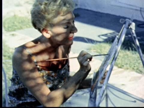 vídeos de stock, filmes e b-roll de actress mary martin sitting in shade in summer dress painting on easel with long thin brush / hamilton bermuda - só uma mulher idosa