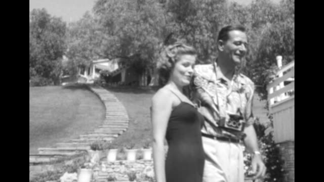 "actress nancy olson, newly crowned ""miss stereo,"" steps to join john wayne, who wears a loud patterned shirt and stands next to a swimming pool with... - actress stock videos & royalty-free footage"