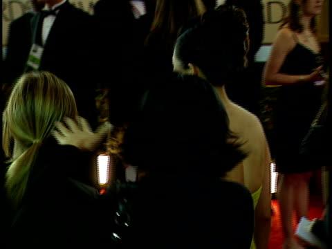 Actress Zhang Ziyi walking through crowded red carpet at Beverly Hilton hotel posing w/ yellow dress