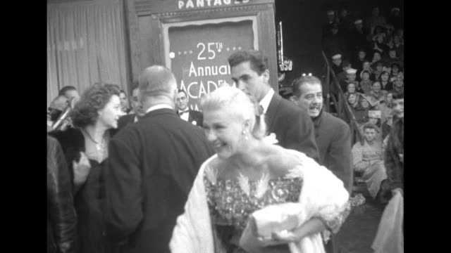 actress/dancer ginger rogers arrives at the pantages theater and greets people as a police officer stands nearby - パンテージスシアター点の映像素材/bロール
