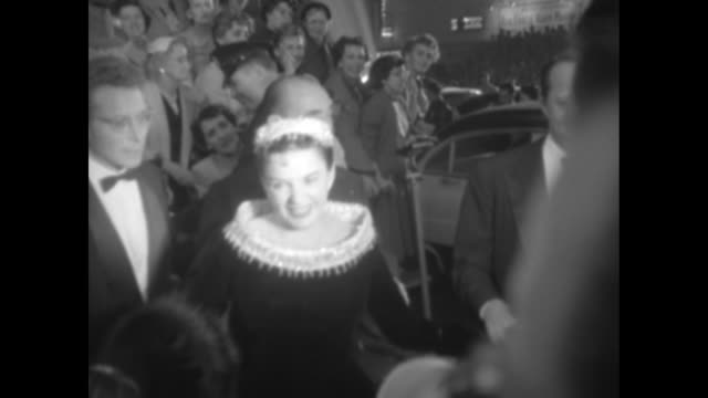 Actress/entertainer Judy Garland arrives at the premiere of her film A Star is Born holding the hand of husband Sidney Luft and followed by Warner...
