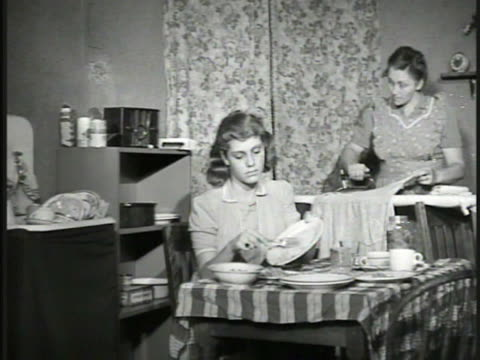 stockvideo's en b-roll-footage met ad in paper for radio program 'experiences teaches' dramatization urban mother ironing w/ listless daughter at kitchen table scraping dishes cu small... - strijkijzer