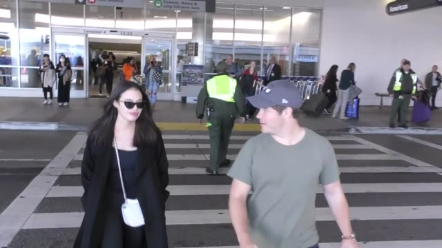 INTERVIEW Adam DeVine and Chloe Bridges talk about their trip to Hawaii as they arrive at Los Angeles International Airport at Celebrity Sightings in...