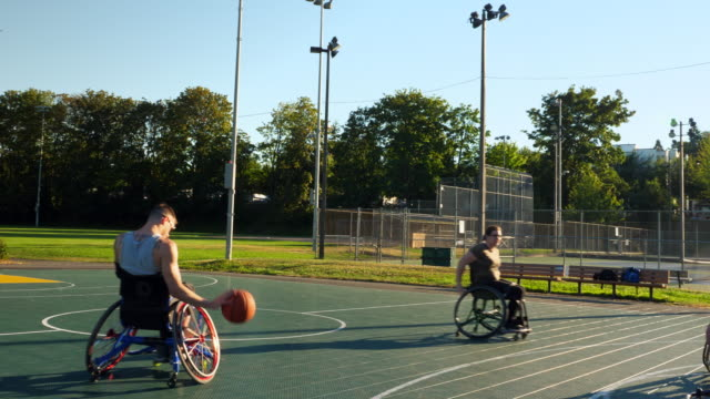 ts adaptive athlete dribbling basketball on outdoor court during game on summer evening - wheelchair basketball stock videos and b-roll footage