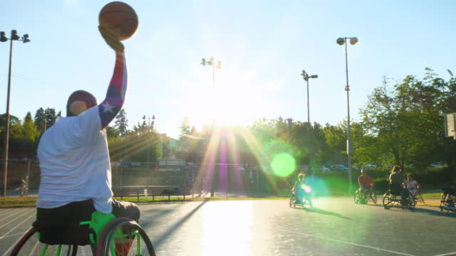 ts adaptive athlete dribbling basketball on outdoor court during game on summer evening - drive ball sports stock videos & royalty-free footage