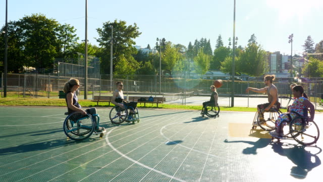 ms adaptive athlete dribbling basketball on outdoor court during practice - wheelchair basketball stock videos and b-roll footage