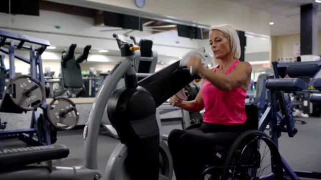 Adaptive athlete in a wheelchair using a seated cycling machine