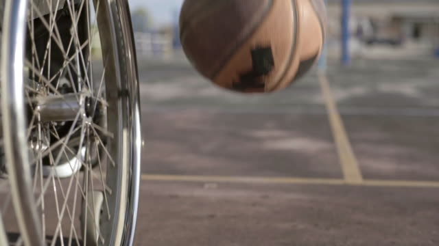 adaptive athlete in wheelchair playing basketball - disability stock-videos und b-roll-filmmaterial