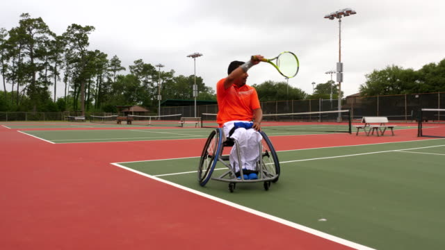 ms la adaptive athlete moving across court during wheelchair tennis match - racket stock videos and b-roll footage