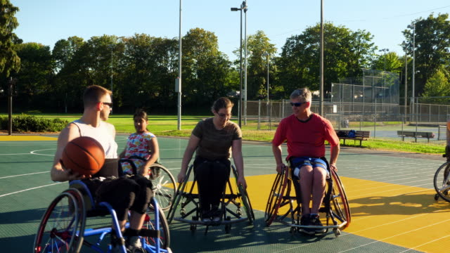 ms adaptive athlete passing ball to teammate during wheelchair basketball practice on summer evening - wheelchair basketball stock videos and b-roll footage
