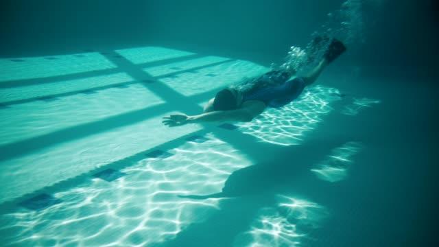 vídeos de stock e filmes b-roll de adaptive athlete practicing backstroke starts. - desporto aquático