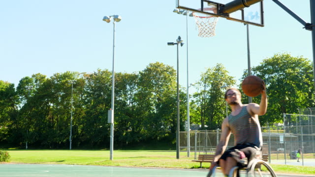 ms adaptive athlete practicing shoting while warming up for wheelchair basketball practice on summer evening - wheelchair basketball stock videos & royalty-free footage