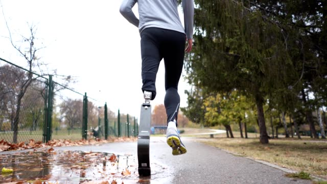 adaptive athlete running outdoors in autumn - prosthetic equipment stock videos & royalty-free footage