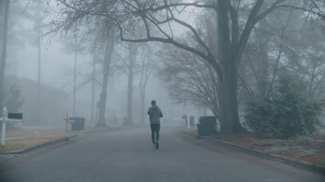 slo mo adaptive athlete runs along residential road at dawn - endurance stock videos & royalty-free footage
