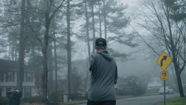 adaptive athlete runs around a residental street corner during an early morning excercise - pursuit concept stock videos & royalty-free footage