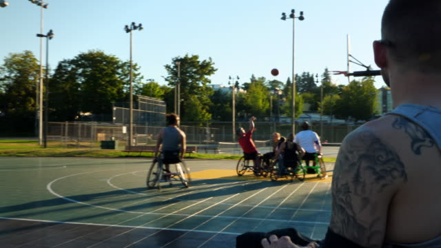 ms adaptive athlete taking a break from basketball game on sideline of outdoor court - wheelchair basketball stock videos and b-roll footage
