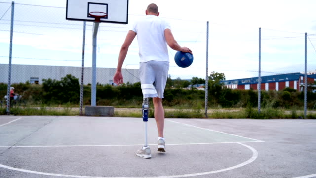 adaptive athlete taking a shot at basketball court - amputee stock videos & royalty-free footage