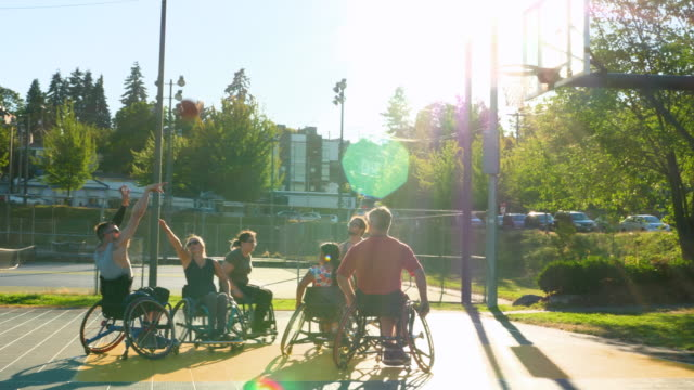 ms adaptive athlete taking shot during wheelchair basketball game on outdoor court - wheelchair basketball stock videos and b-roll footage