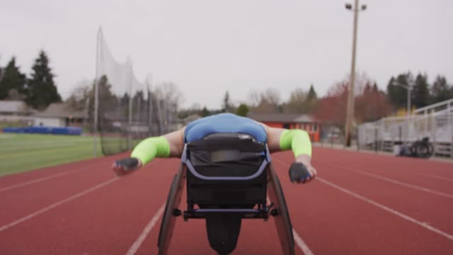vídeos de stock e filmes b-roll de adaptive athlete training on his racing wheelchair - support